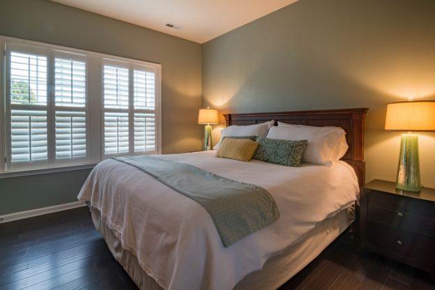 Kæmpe seng med brunt træ og flot sengebetræk